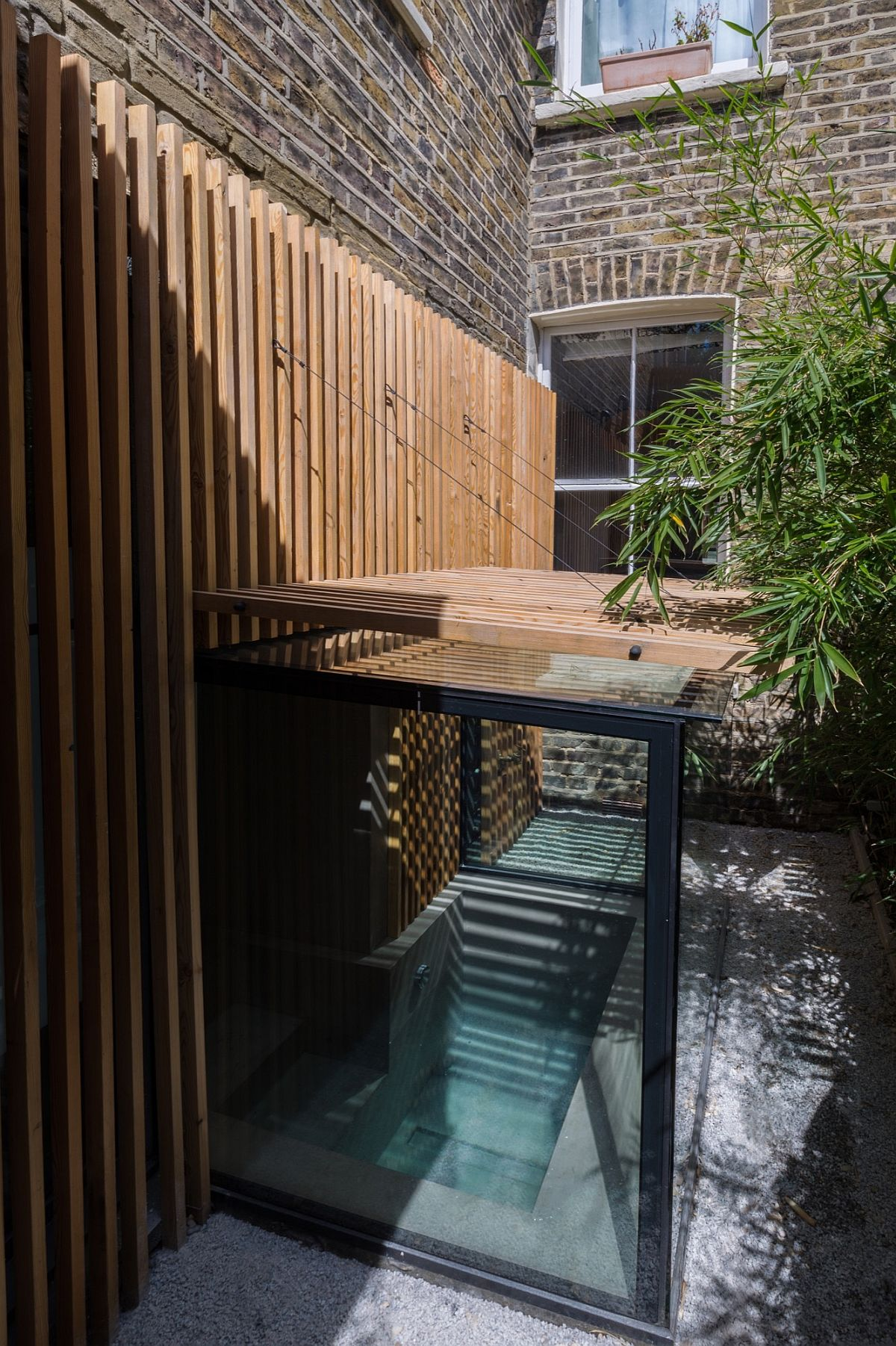 Glass walls connect teh sunken bath with the garden even as the slatted larch screen offers privacy