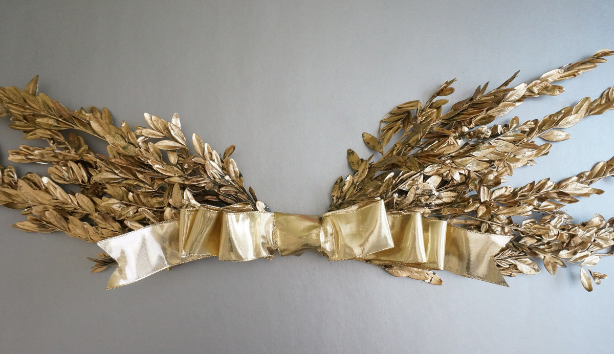 Gold holiday wall hanging with a bow