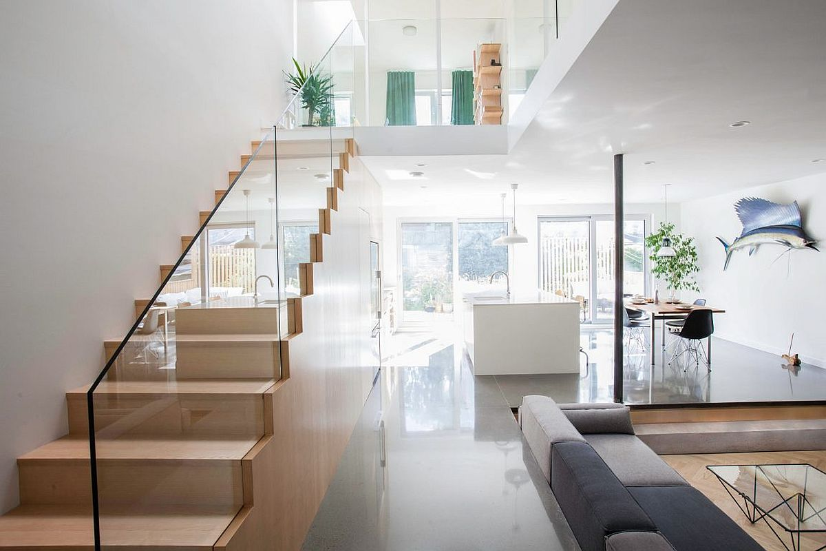Gorgeous wooden staircase with glass railing also offers plenty of storage space