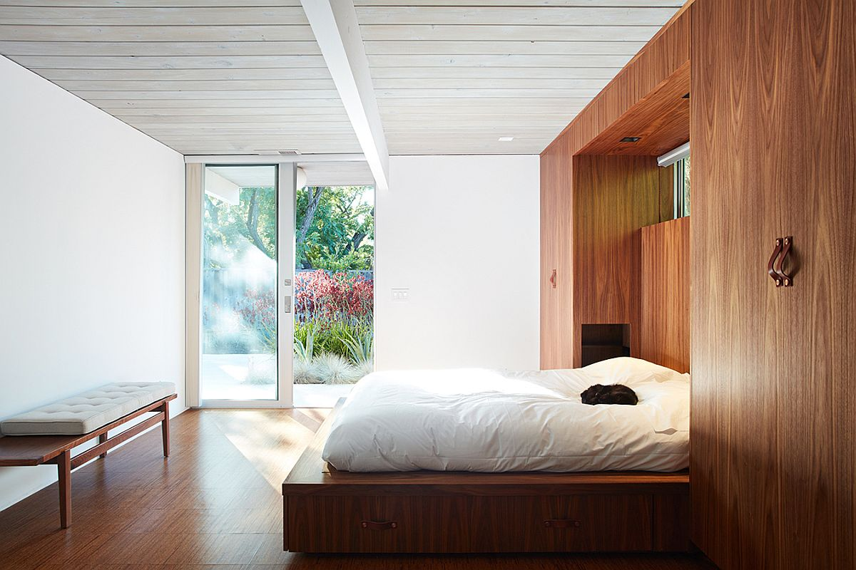 Head of the bed tucked within the wooden wardrobes
