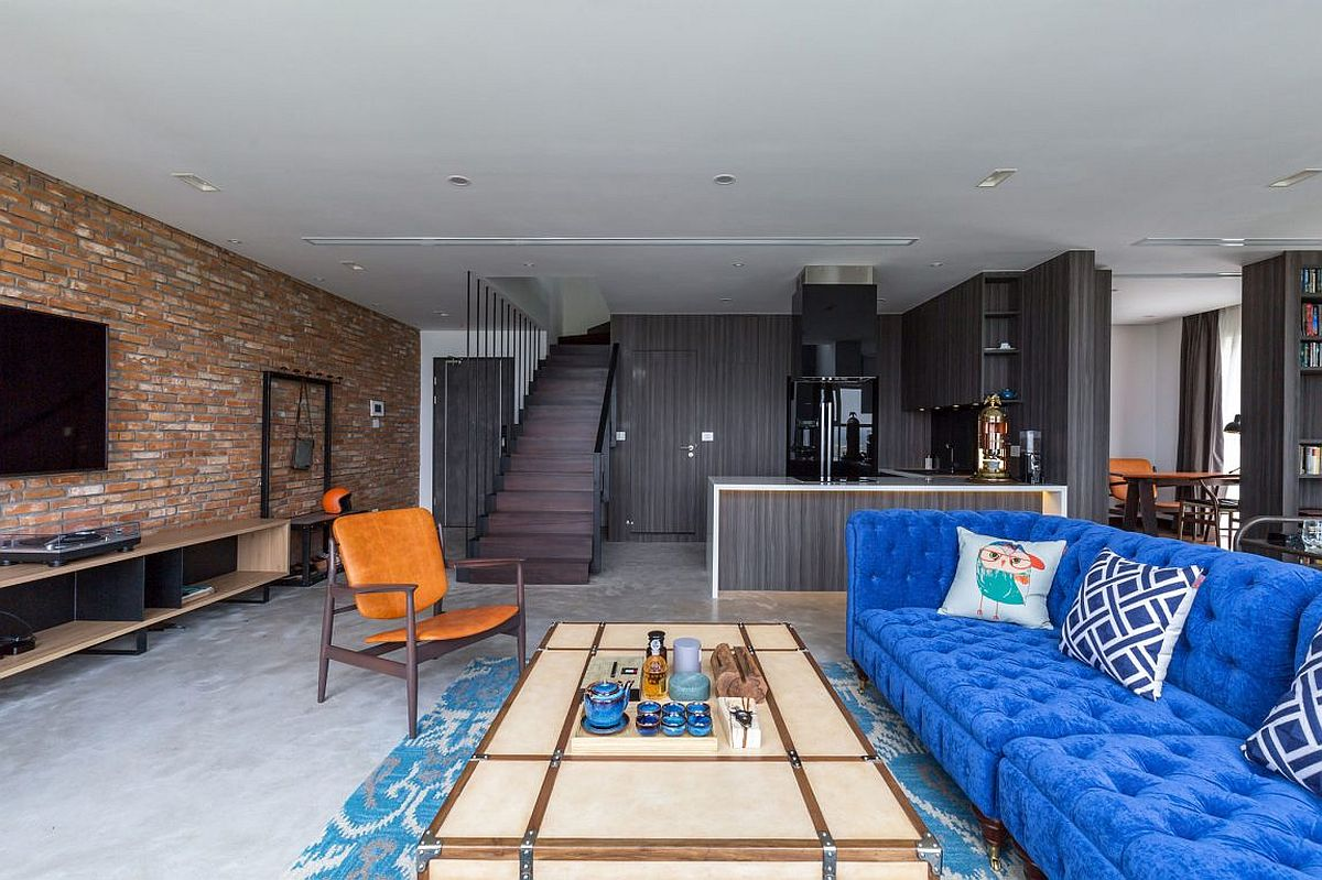Industrial living room with brick wall and bright blue couch