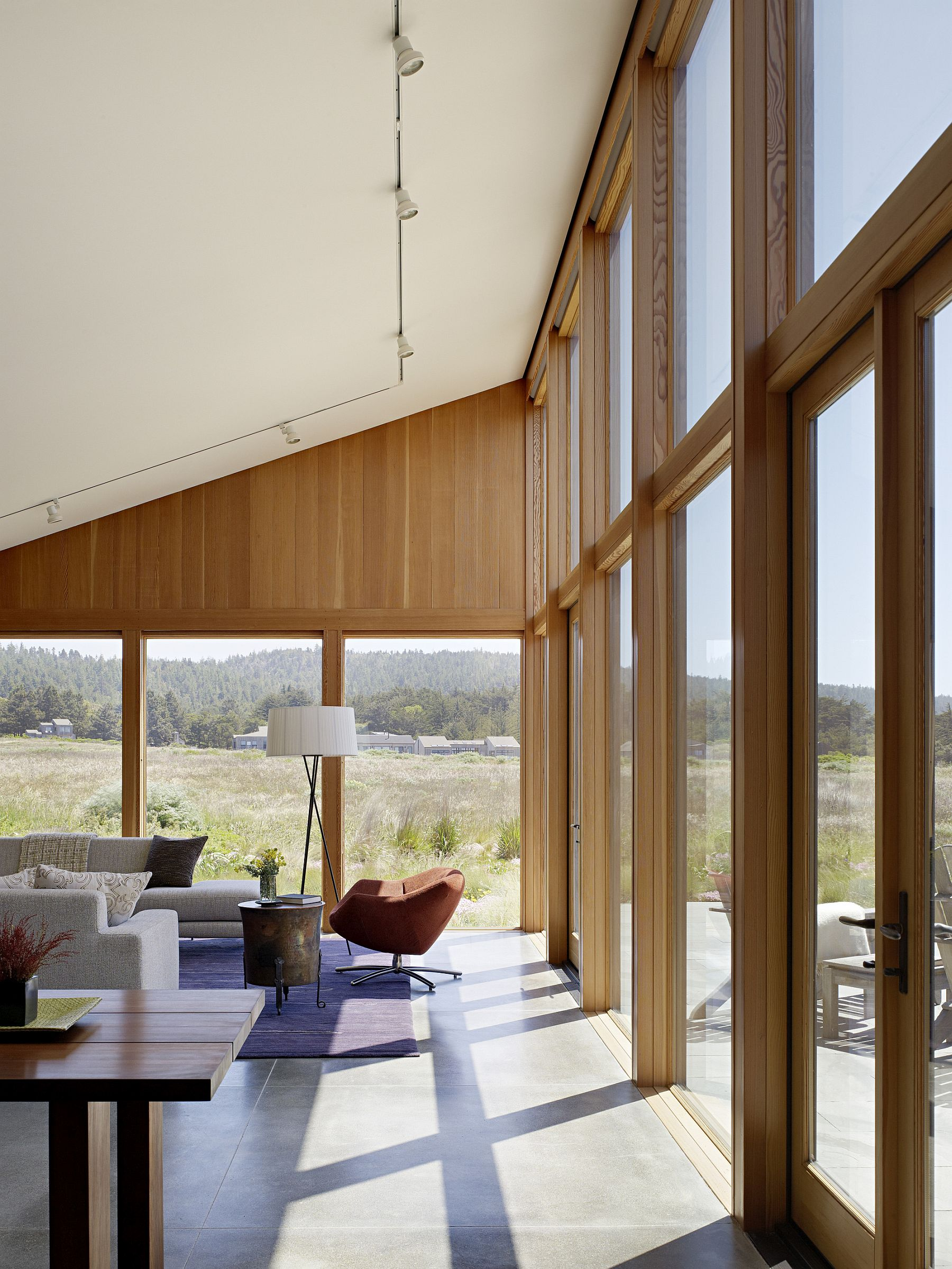 Large windows and glass doors connect the interior with the fabulous view outside