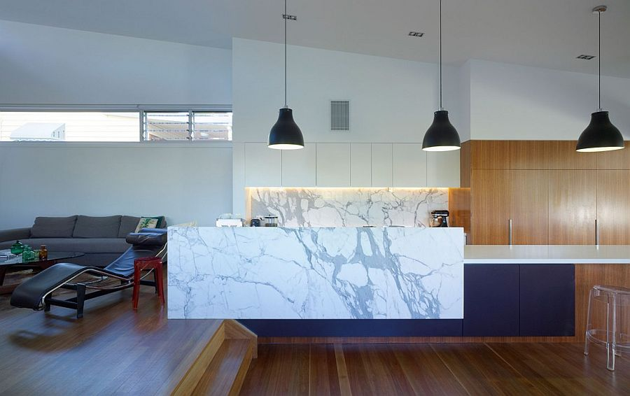 Marble kitchen island complements the marble backsplash of the stylish space perfectly