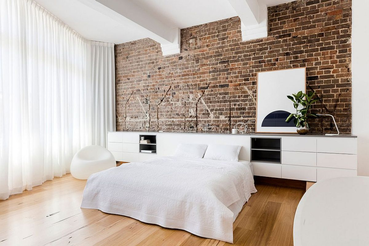 Modern bedroom in white with exposed brick wall