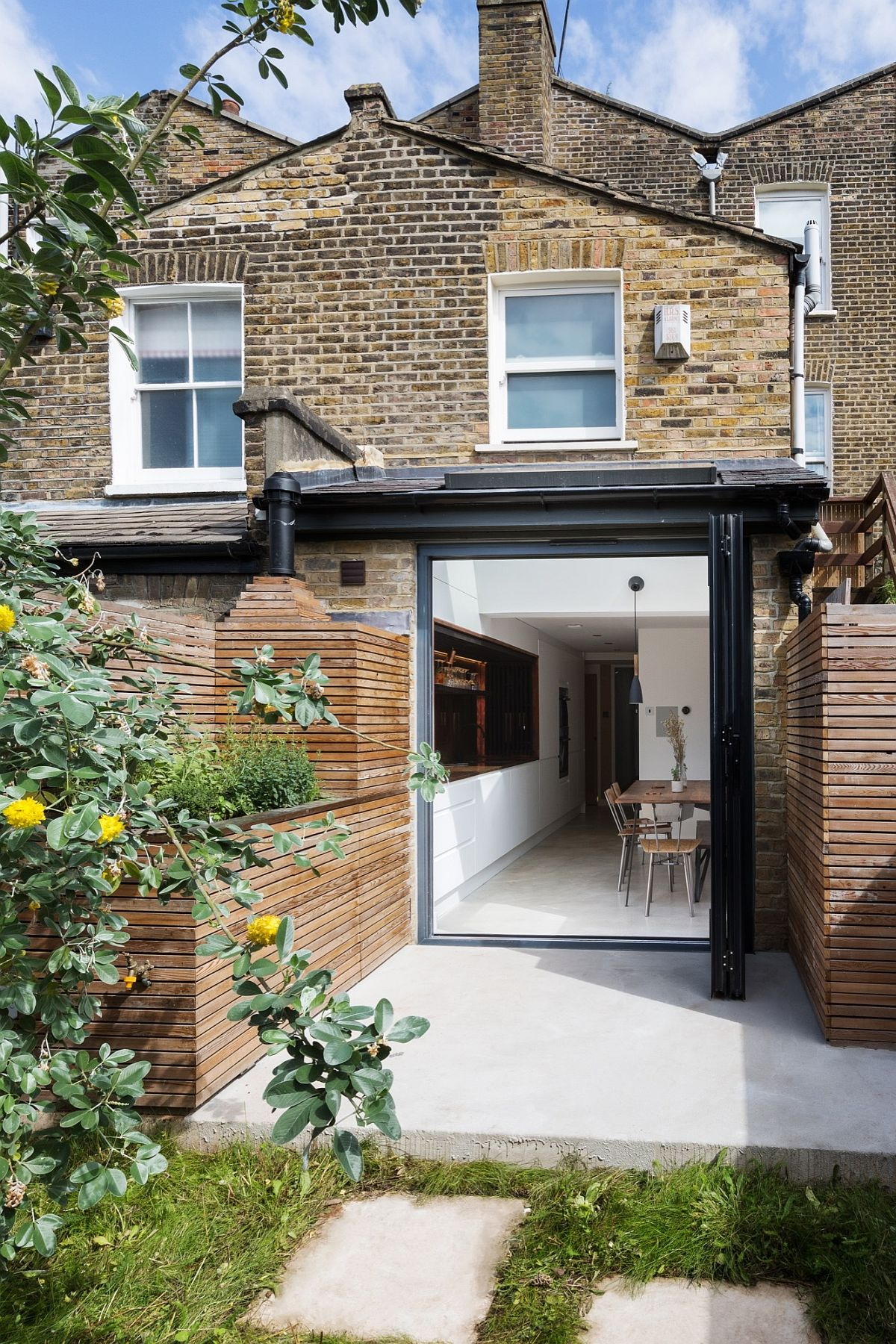 New kitchen, dining and sunken bath of the London home extend into the garden outside