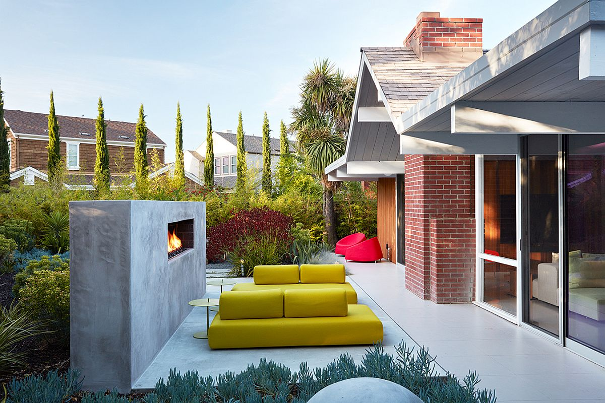 Outdoor hangout with bright yellow seating and contemporary fireplace