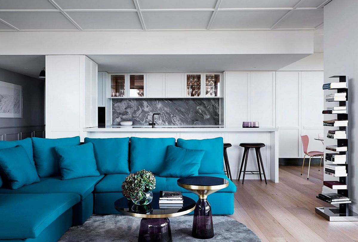 Peacock blue upholstered circular lounge in the living room Posh Penthouse Makeover in Melbourne Relies on Chic Décor and LA Glamour