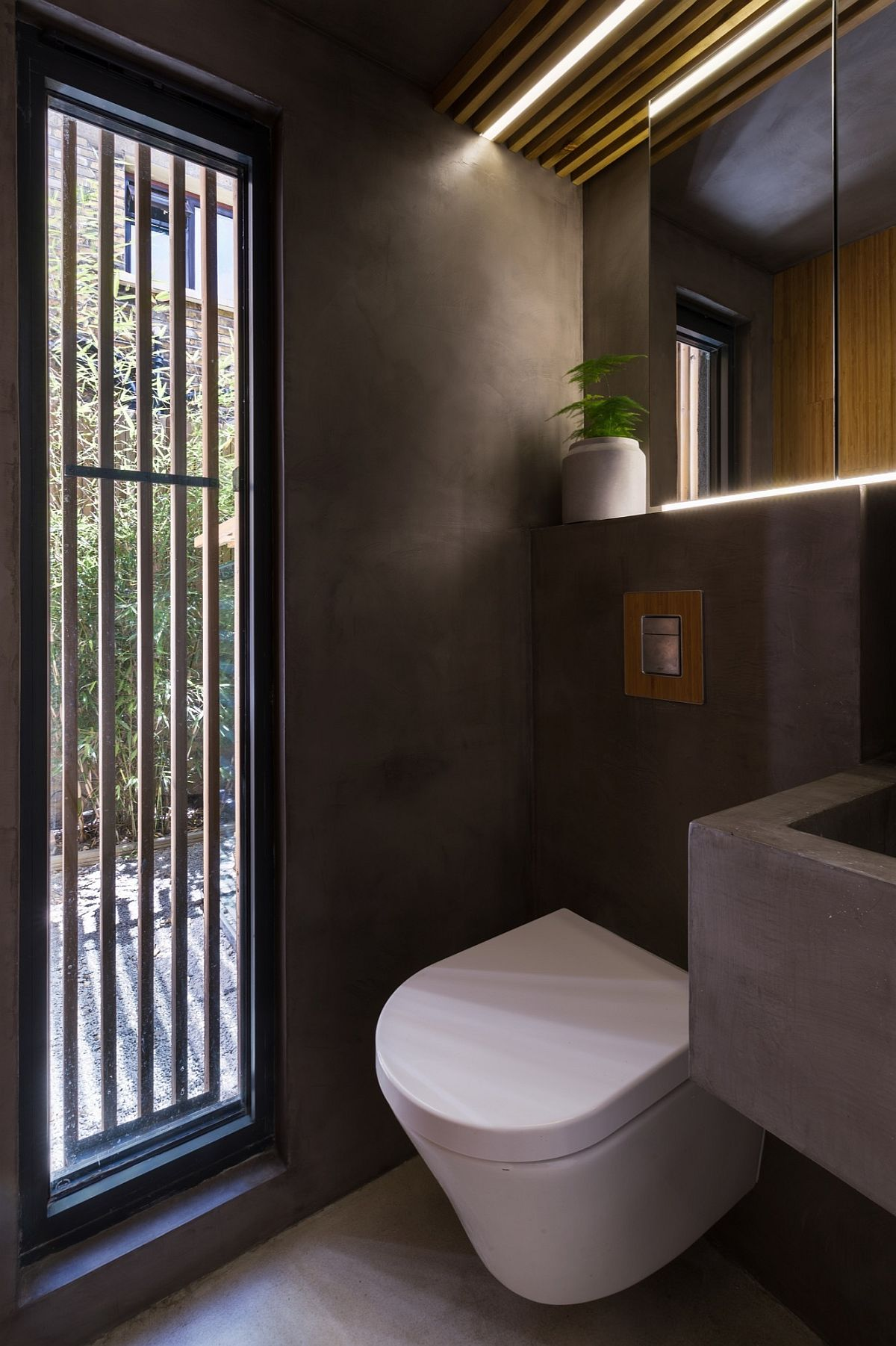 Polished concrete shapes the contemporary bathroom with garden view