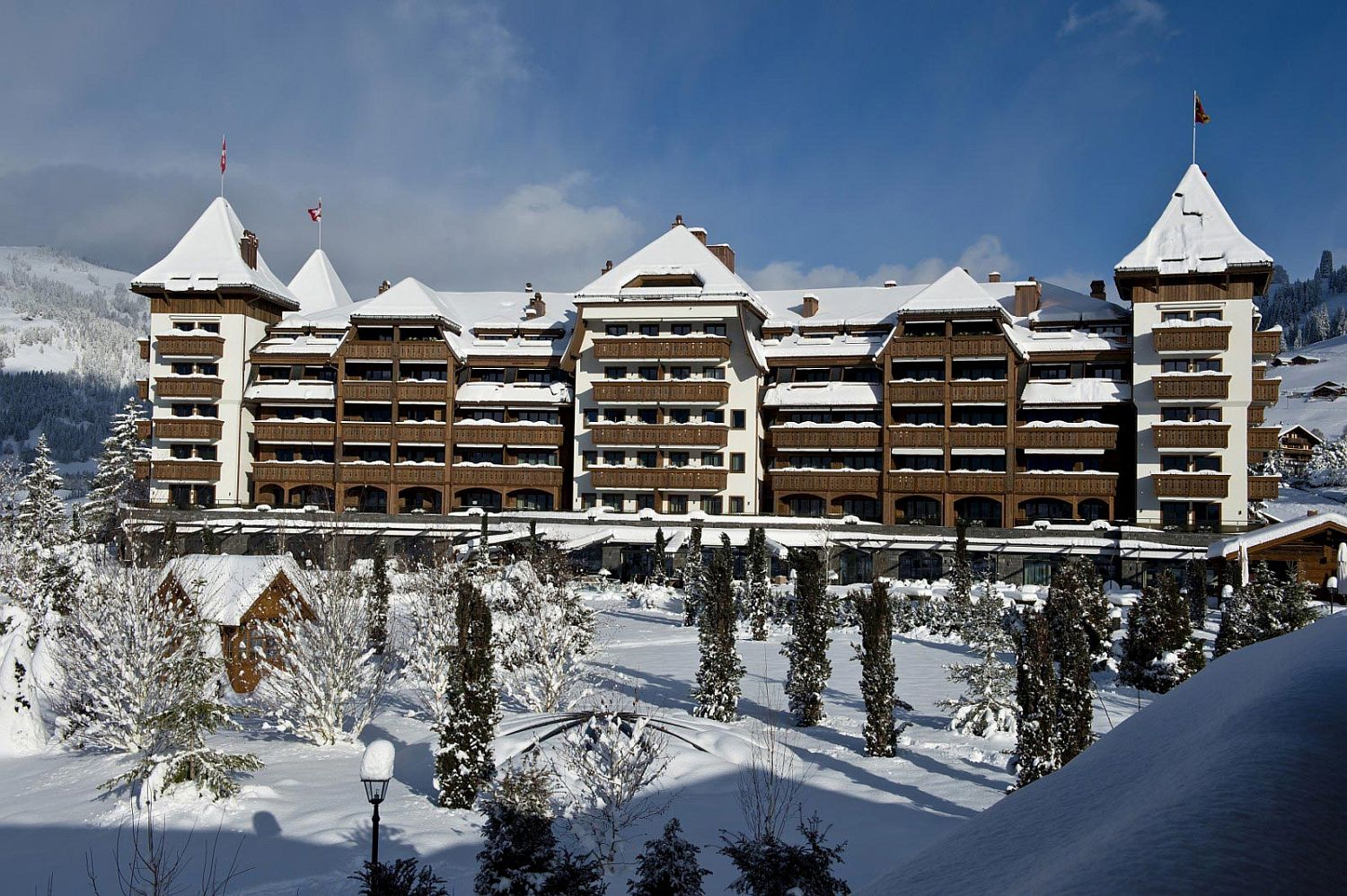 Snow-covered facade of luxurious 5-star hotel - Alpina Gstaad