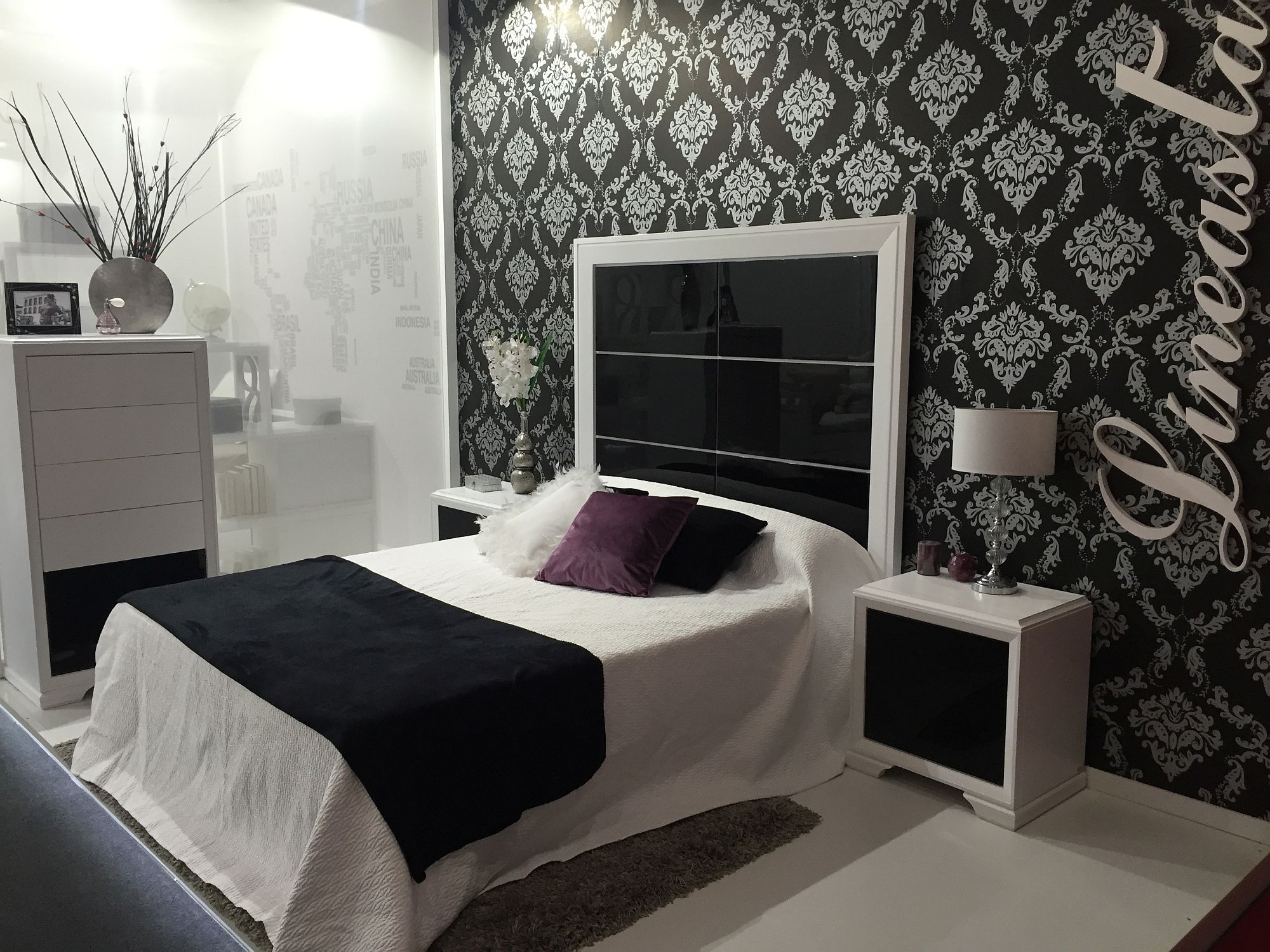 Black and white bed with a glossy, dramatic headboard