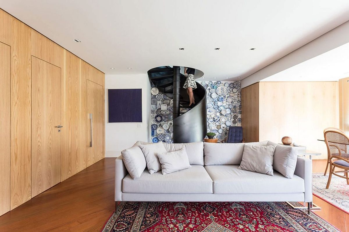 Blue plates create a stunning accent wall behind the spiral staircase Spiral Staircase and Fun Accent Wall Steal the Show at Collector's Apartment