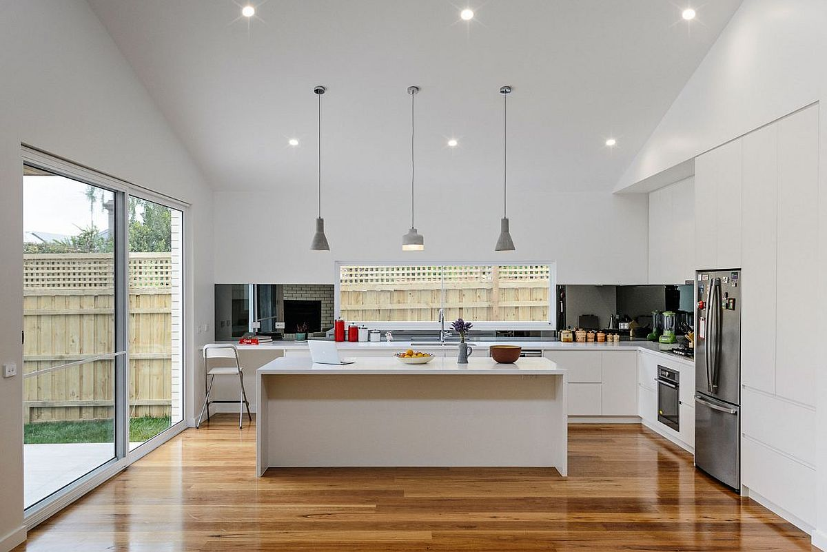 Contemporary kitchen in white with a dark backsplash