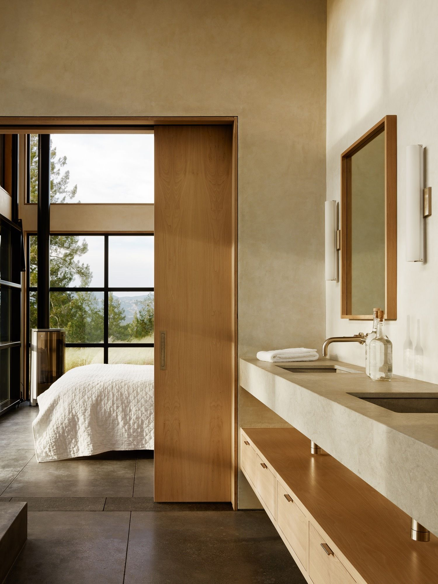 Large glass windows and doors connect the bedroom visually with the gorgeous outdoors