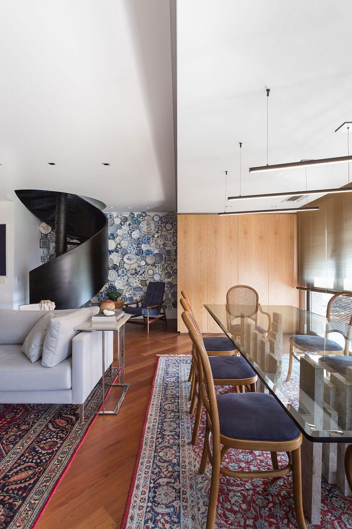 Rugs and accent wall covered with plates add pattern to the modern interior