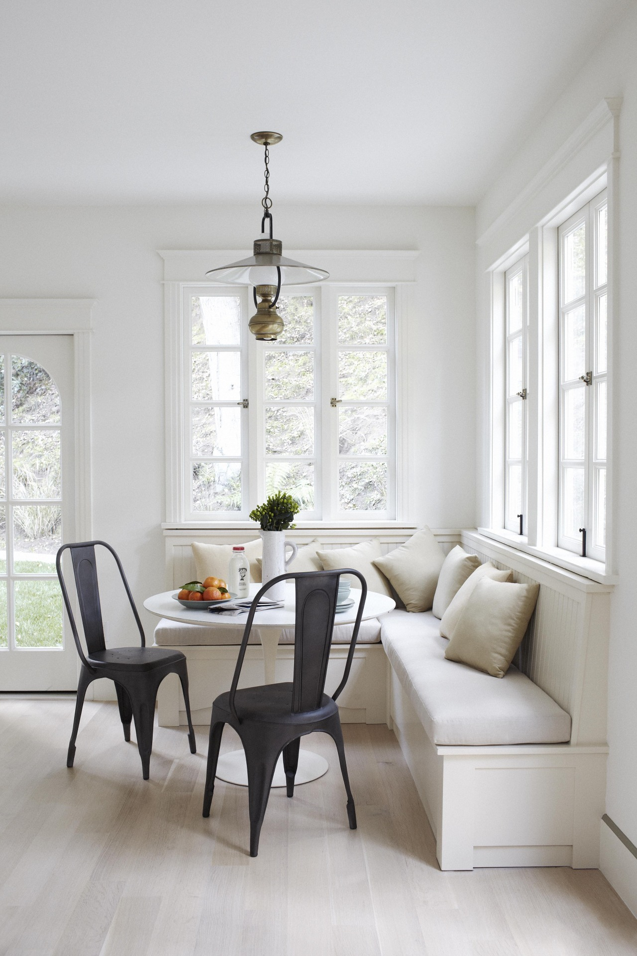 Simplistic banquette paired with dark chairs