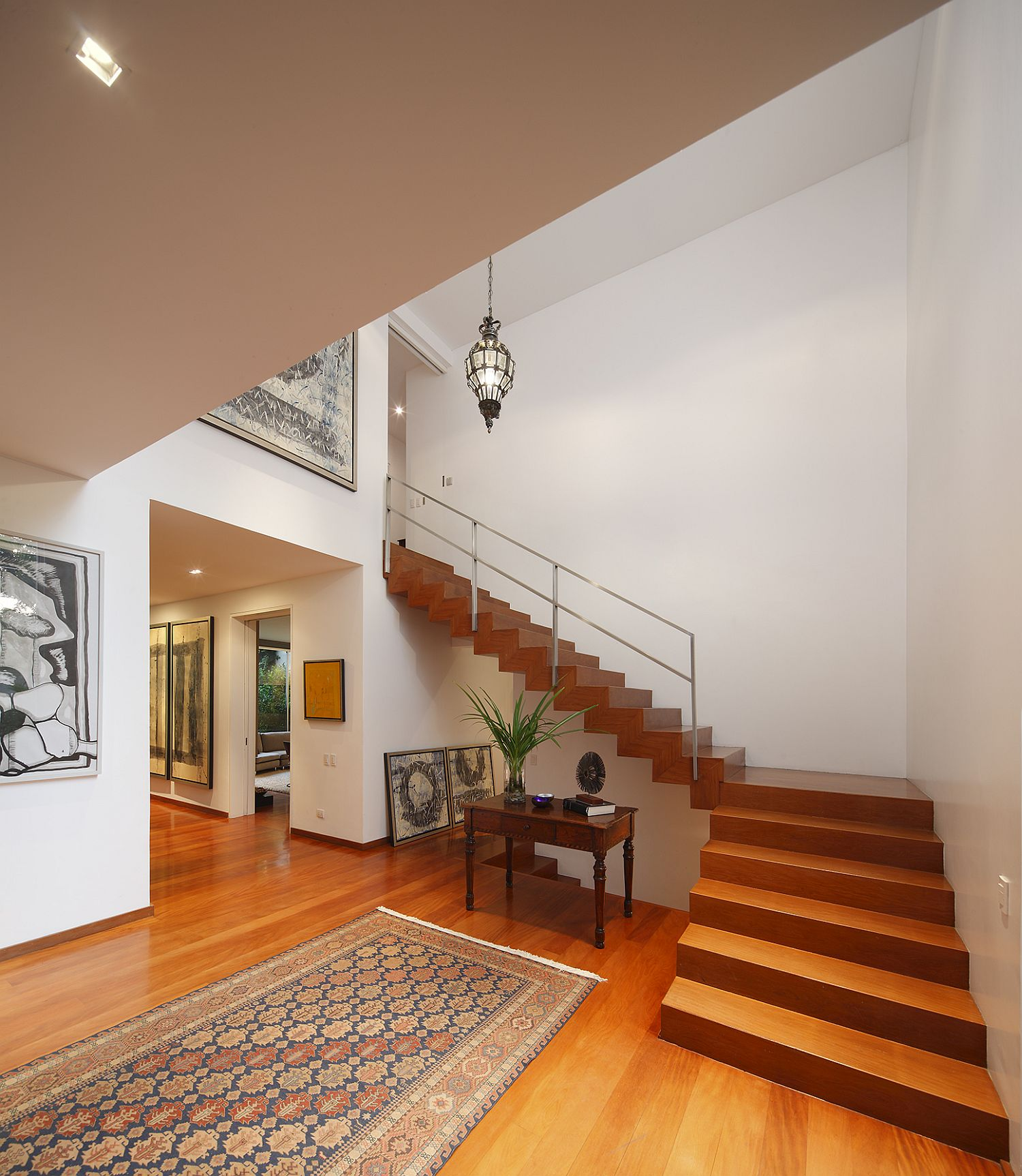 Wooden staircase connects the lower level with the top floor
