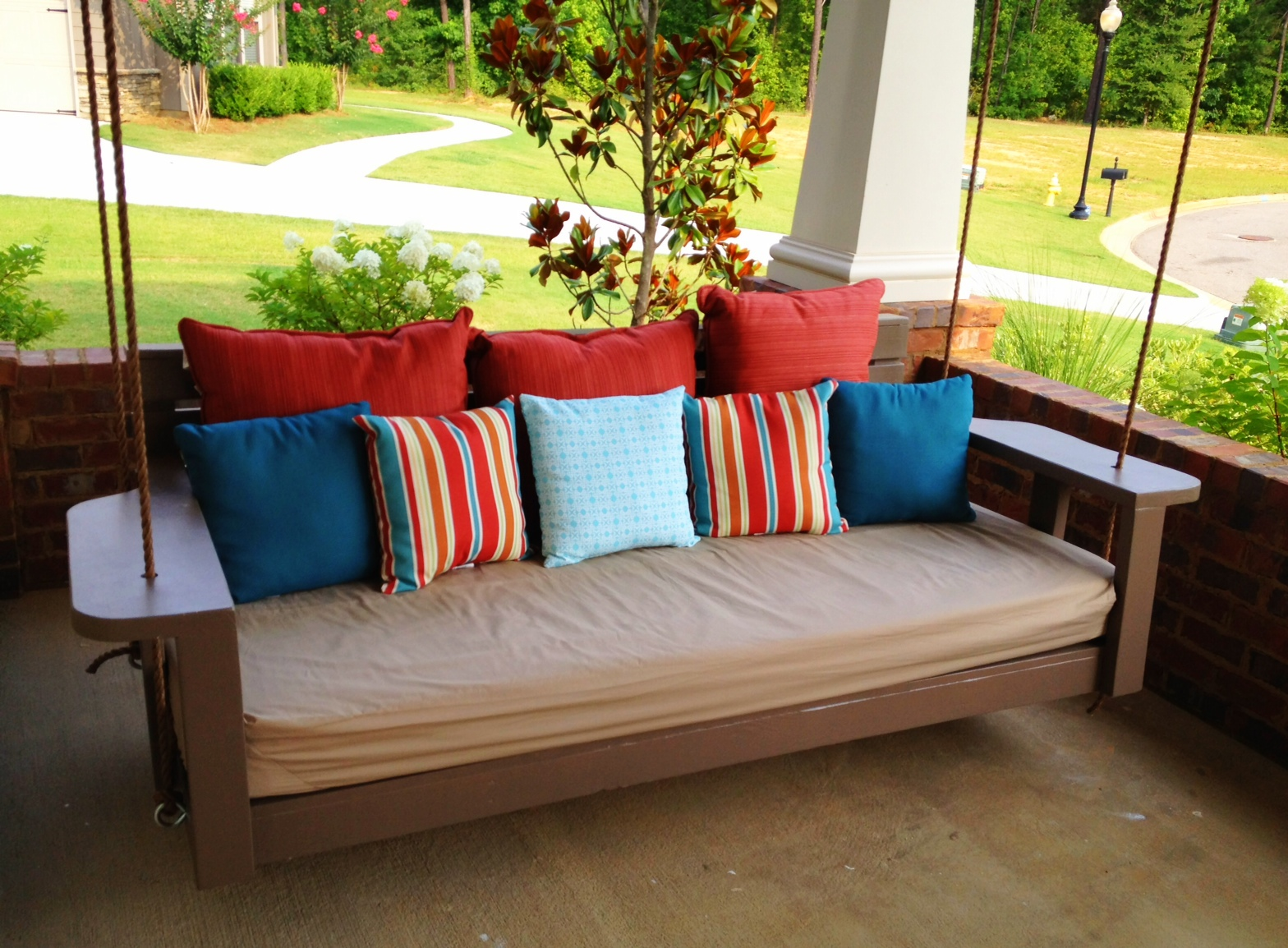 A chestnut brown swing with multicolored cushions
