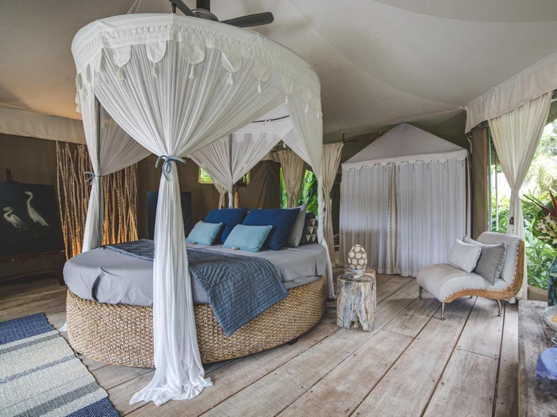 A round four poster bed in an open bedroom