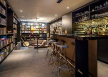 Art-work-wall-of-books-and-a-home-bar-shape-an-intimate-interior-217x155