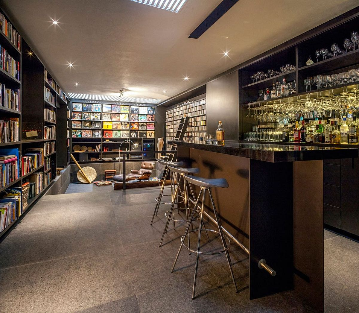 Art work wall of books and a home bar shape an intimate interior