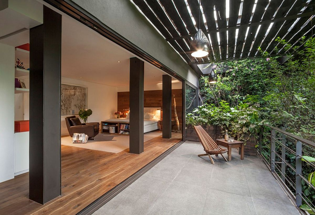 Bedroom opens up completely to the balcony and lush canopy outside