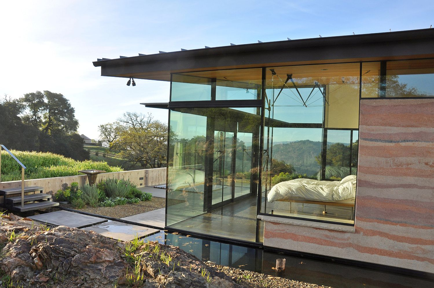 Bedroom with glass walls flows into the patio outside