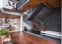 Black polished river pebbles create a unique wall behind the staircase 217x155 Polished Feature Wall with Black River Pebbles Captivates at 22 Toh Yi Road