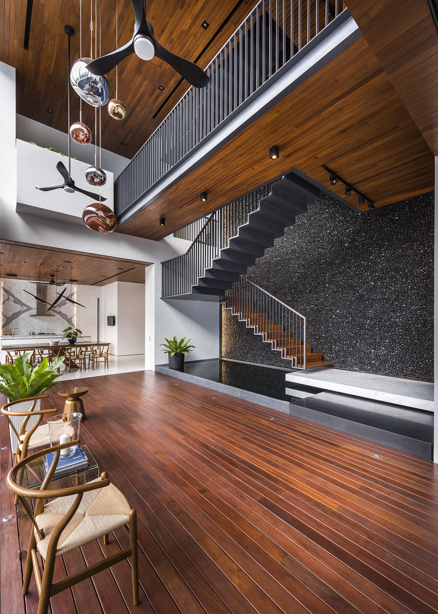 Black polished river pebbles create a unique wall behind the staircase