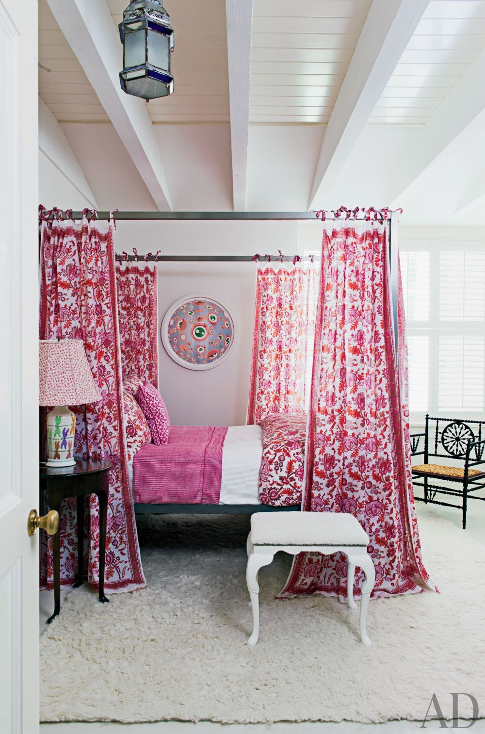 Boho pink four poster bed as the centerpiece of the room