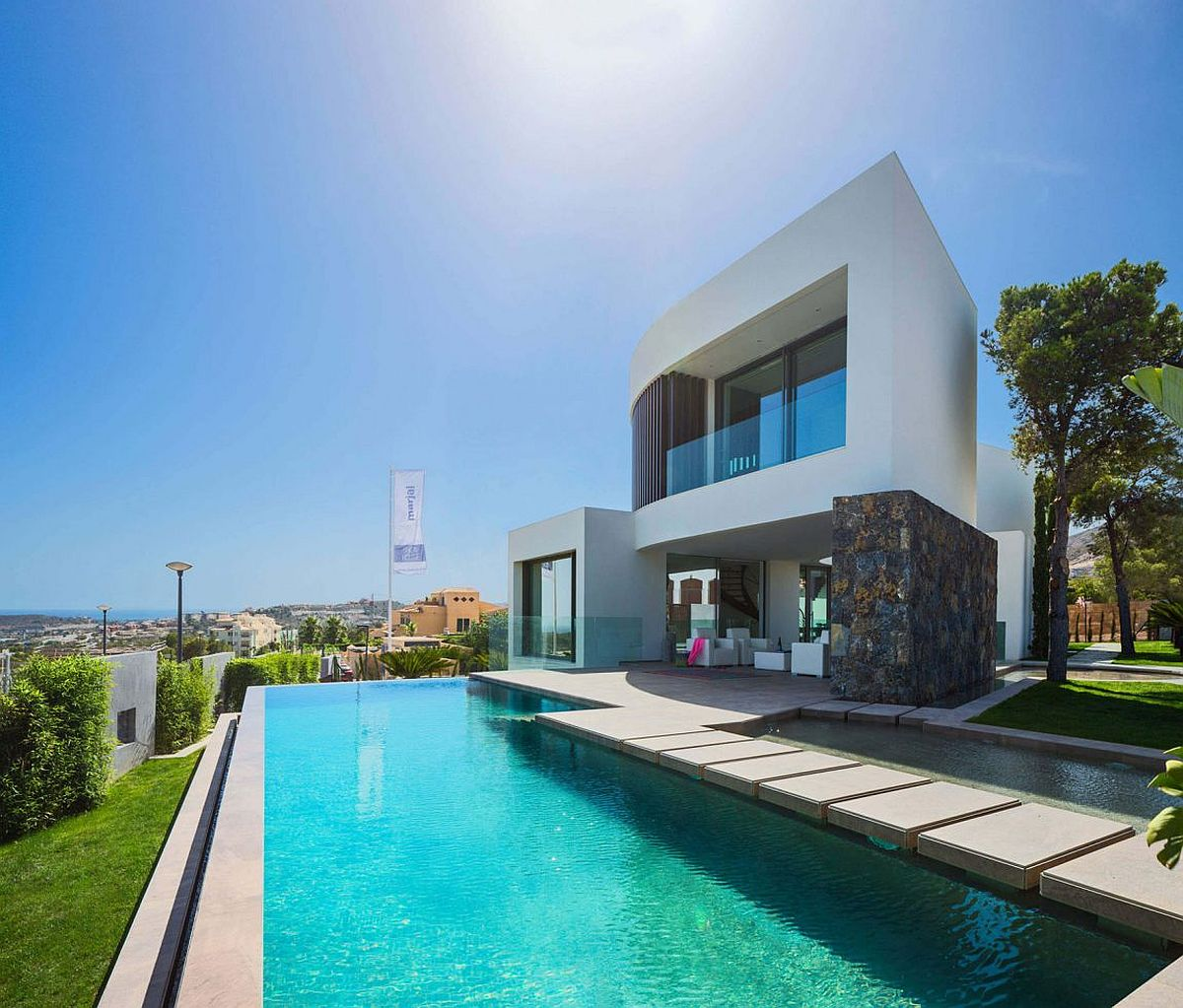 Contemporary pool design with stepping stones adds to the style of the Spanish home
