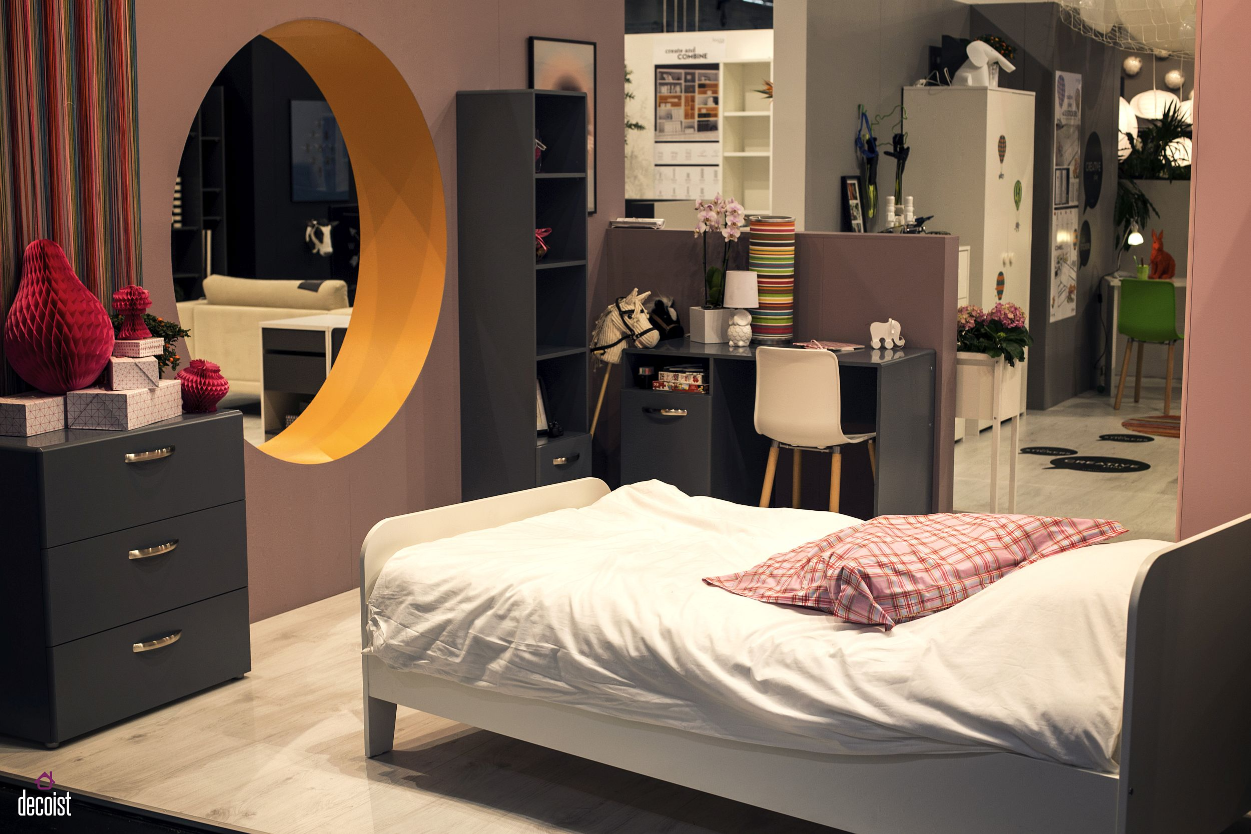 Contemporary teen bedroom idea with a round window, ample storage and a comfy bed