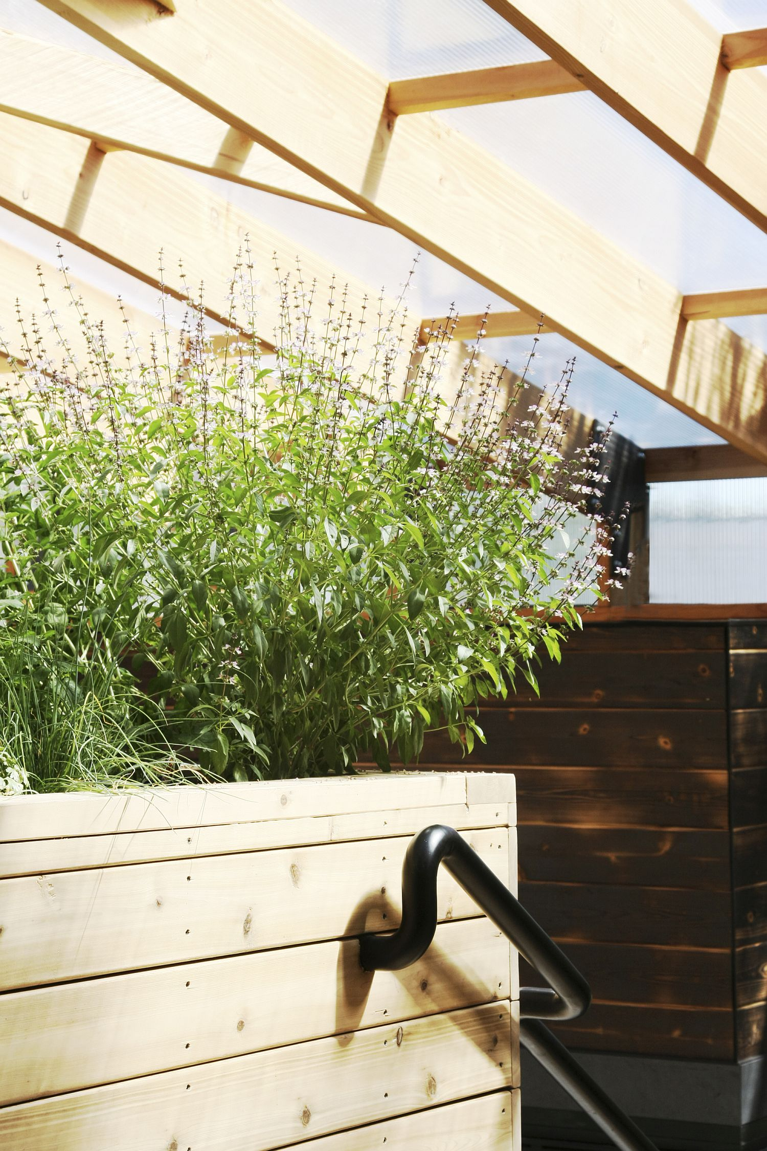 Deck with integrated garden planters is a fun space-saver in the small greenhouse
