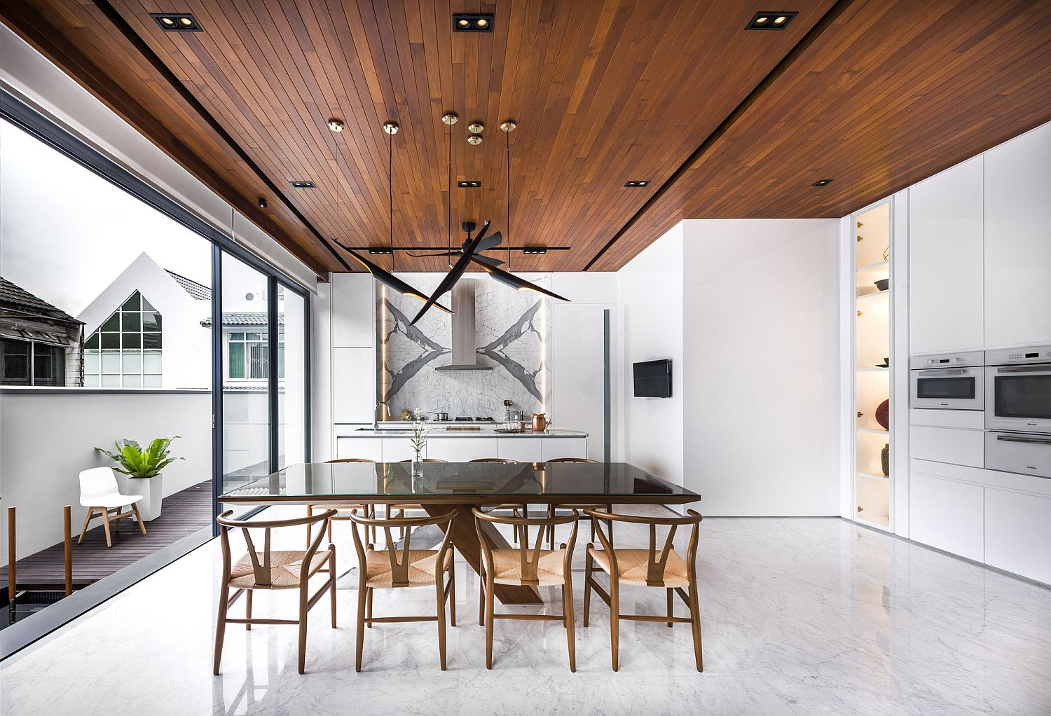 Kitchen and dining space in white with wooden ceiling