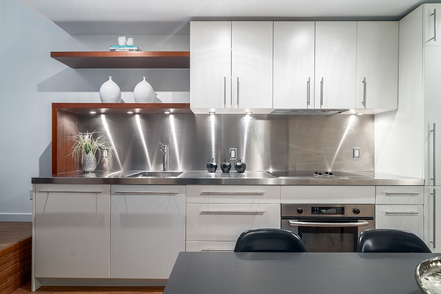 Kitchen with stainless steel backsplash and white cabinets