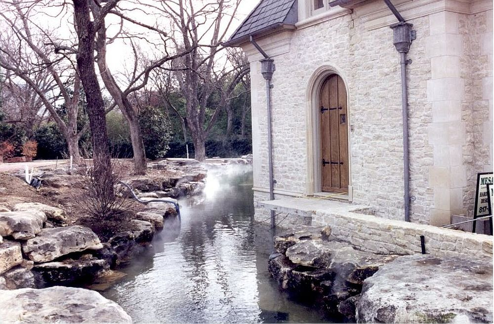 Limestone exterior along with a gentle stream gives the home a dramatic, storybook-inspired look