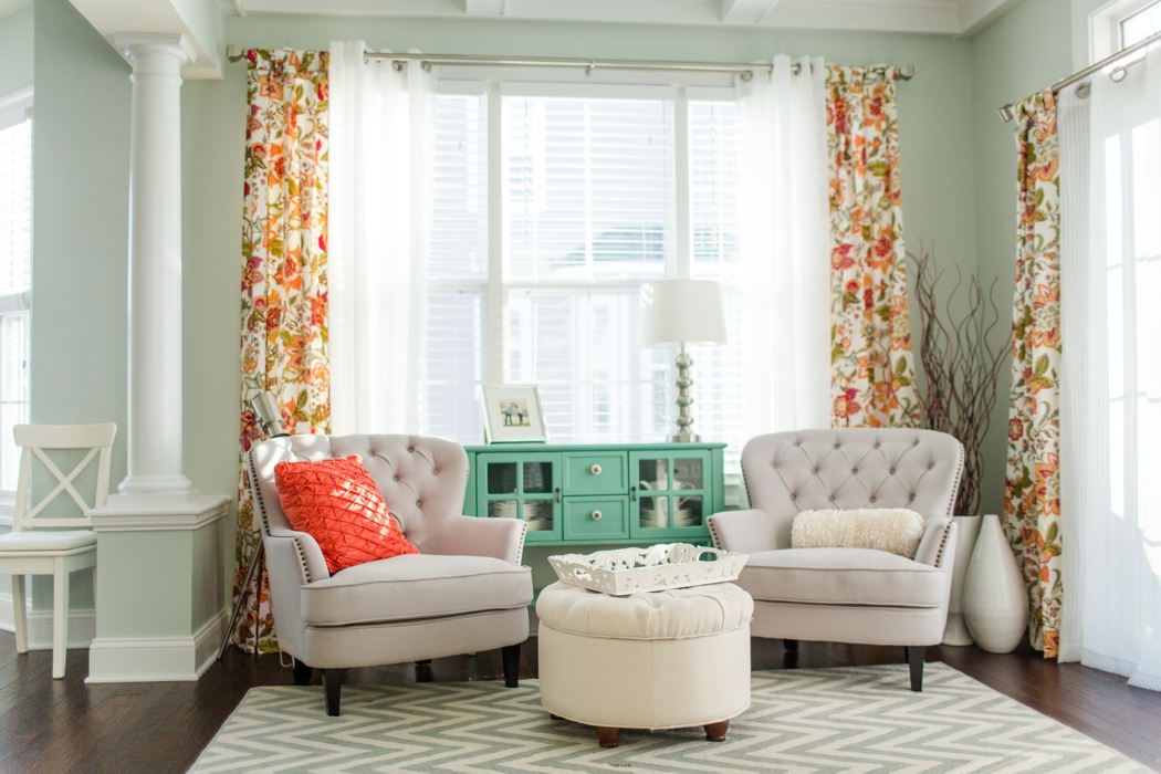 Mint walls with cream armchairs and orange curtains