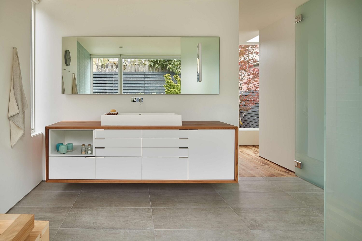 Modern bathroom vanity with wood surround and matching mirror above