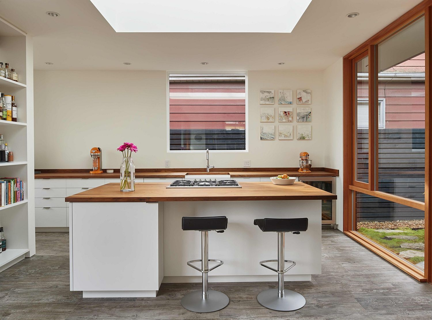 Modern kitchen in white with wooden countertops and ample natural lighting