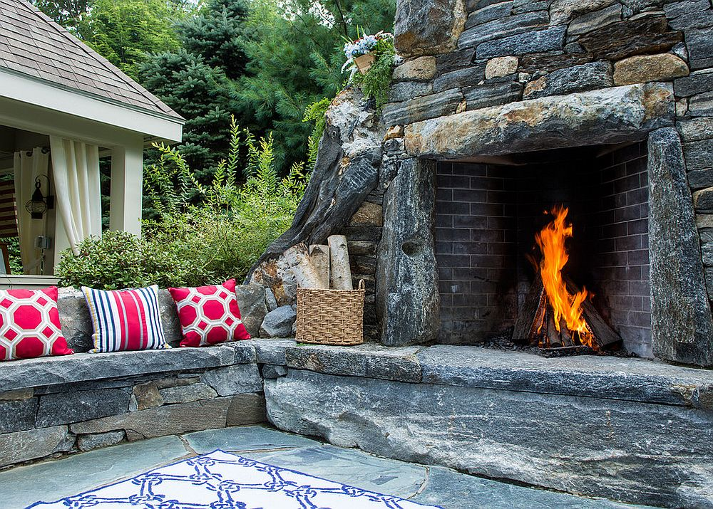 Natural stone fireplace and stone seating shape a stunning outdoor nook