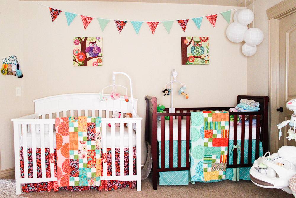 Nursery with two differently colored cribs