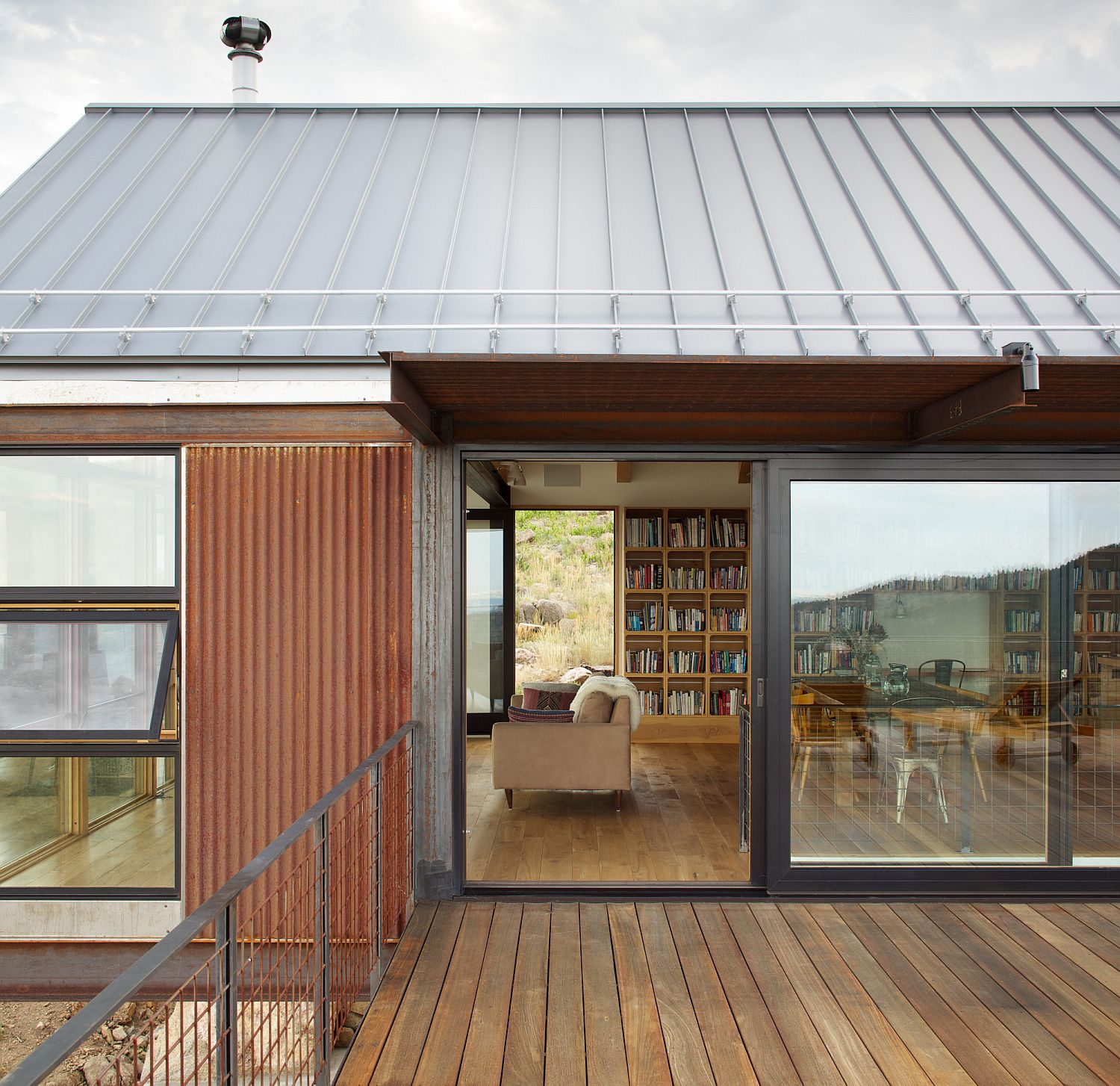 Sliding and framed glass doors connect the living space with the wooden deck at the Sunshine Canyon house