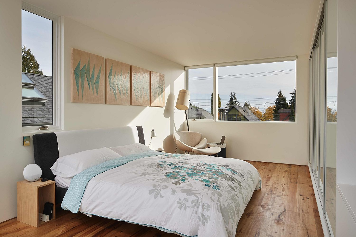 Small bedroom in white with wooden flooring and a series of windows that bring in natural light