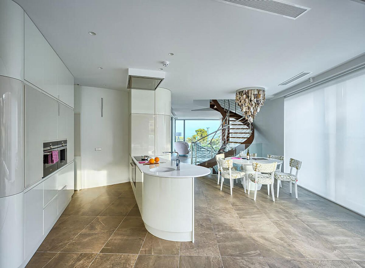 Sophisticated and minimal kitchen and dining space of the Spanish home with a bespoke lighting fixture