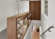 Wooden-shelf-next-to-the-staircase-also-doubles-as-a-railing-217x155