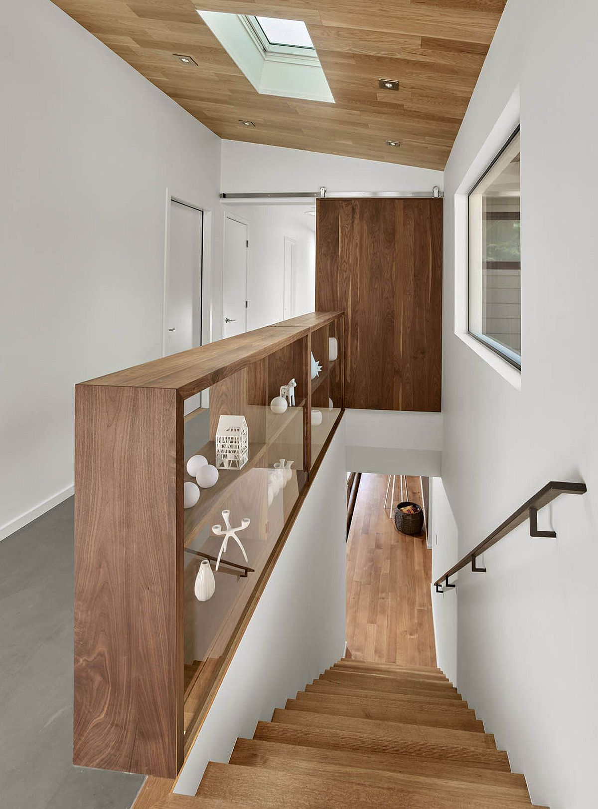 Wooden-shelf-next-to-the-staircase-also-doubles-as-a-railing