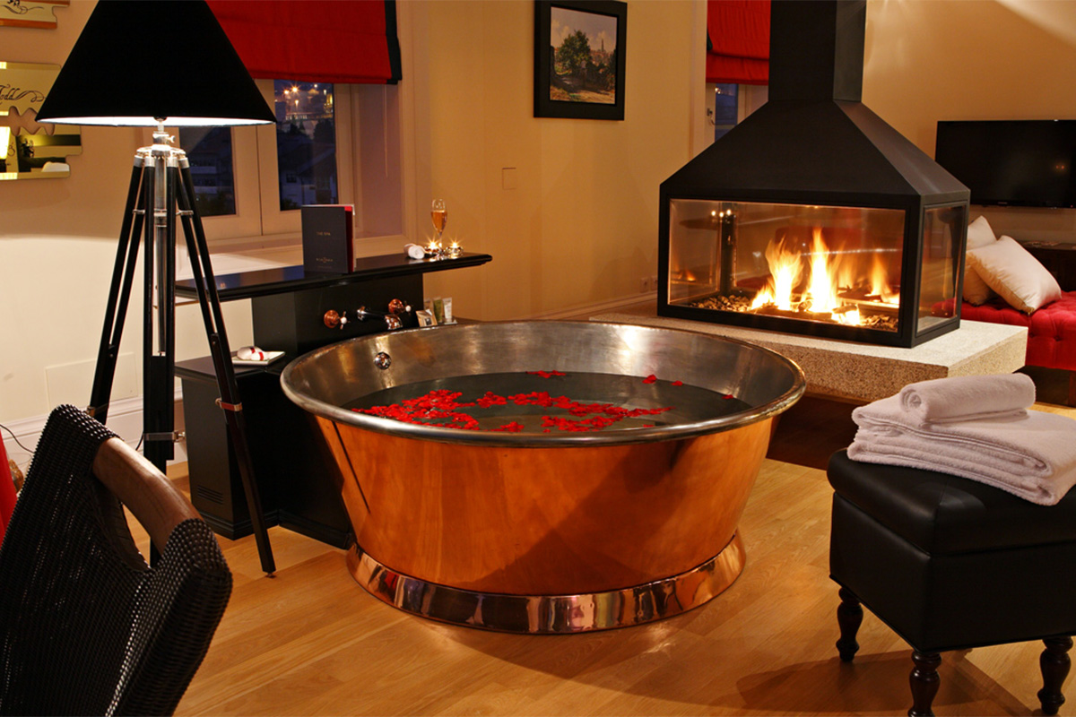 A round copper bathtub in a cozy living room