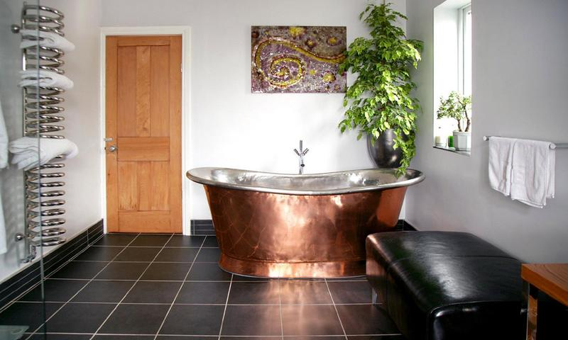 A rustic copper tub in a minimalist bathroom