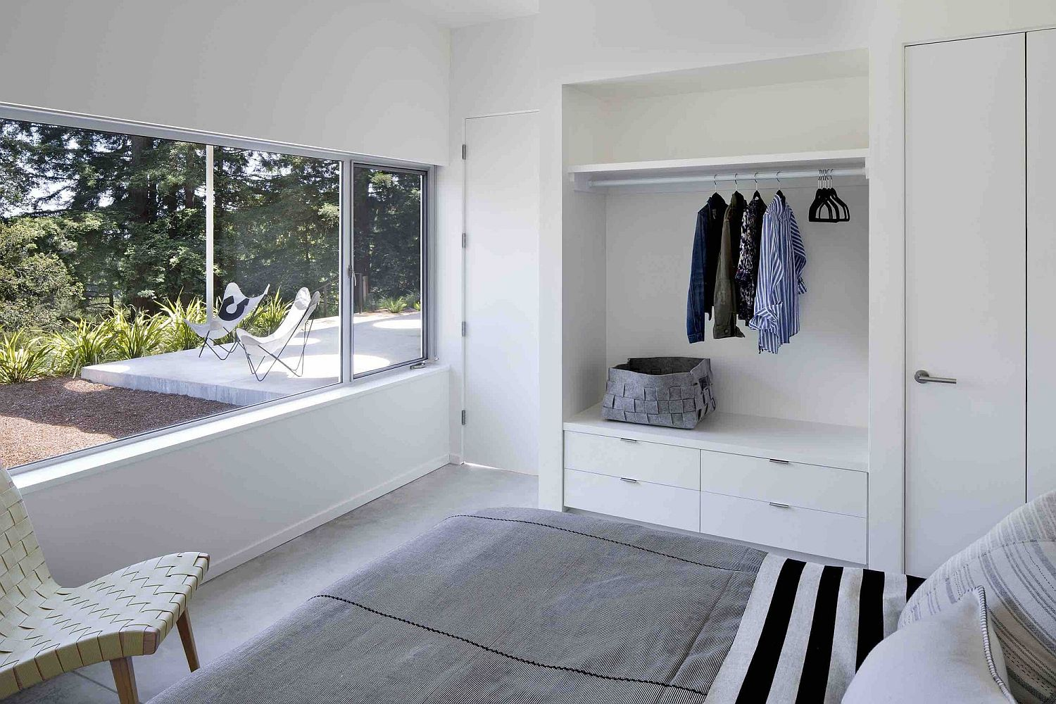 Bedroom in white is tucked away at the rear of the guesthouse to offer privacy