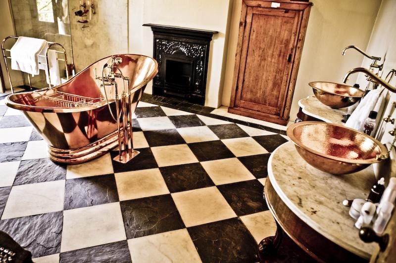 Big-shiny-copper-bathtub-in-the-center-of-an-old-fashioned-bathroom