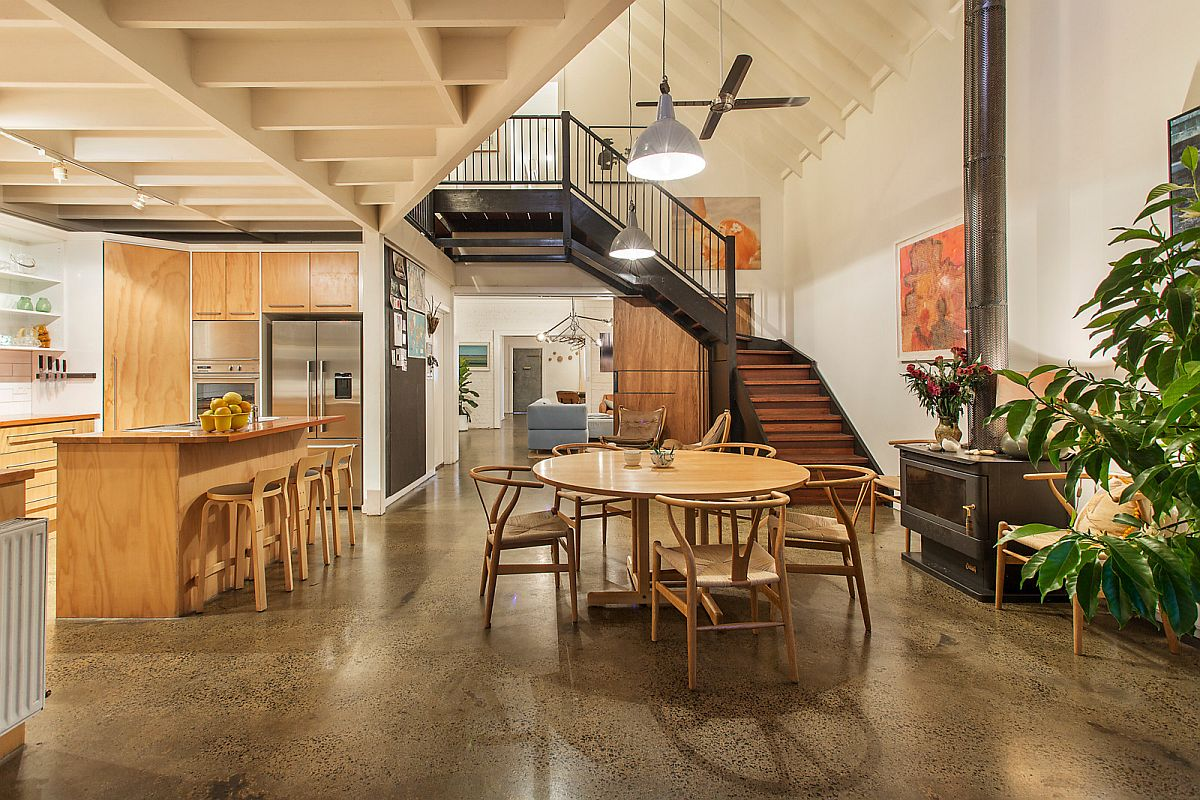 Dining area and kitchen of the renovated warehouse residence embrace wood